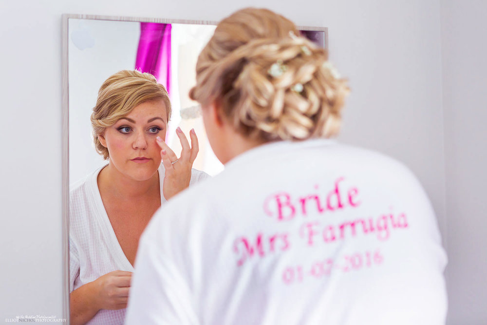 Bride looking into mirror while getting ready