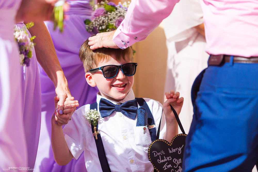 Pageboy outside the church with his wedding sign