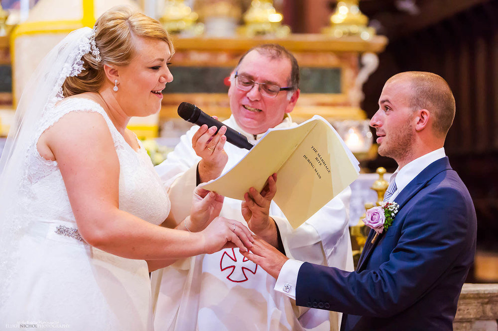 bride says her vows while putting on the grooms wedding ring