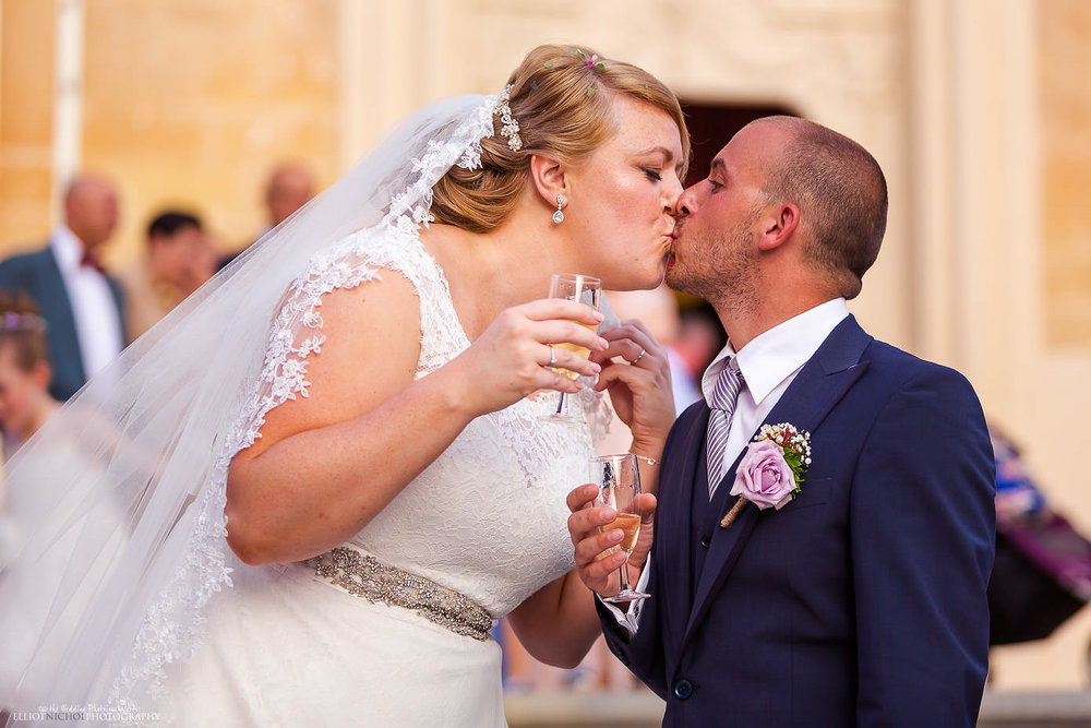 Bride & Groom kissing after drinking champagne