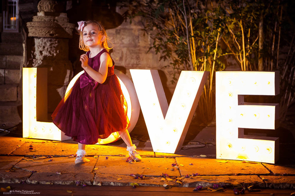 Young wedding guest dancing in front of a love sign