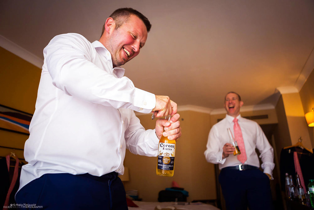 Groom opens a beer while getting ready with his groomsmen.