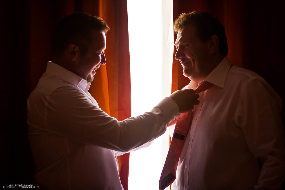 Groom ties his fathers tie in the Corinthia Hotel in St Julians, Malta-