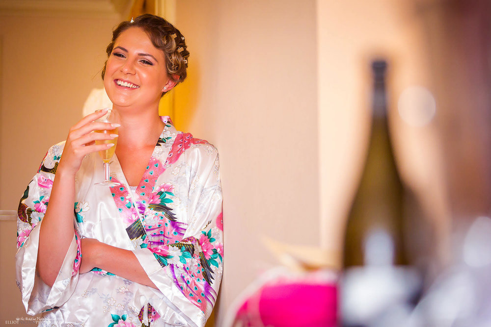 Bridesmaid drinking a glass of champagne in the Corinthia Hotel, Malta