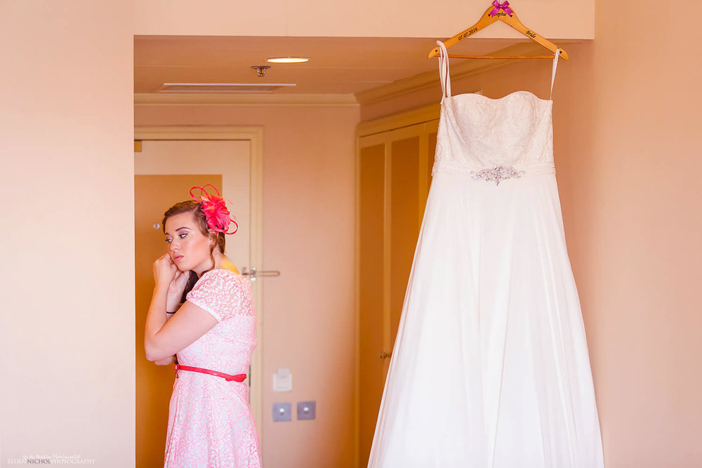 Wedding guest putting in her earrings next to the brides wedding dress