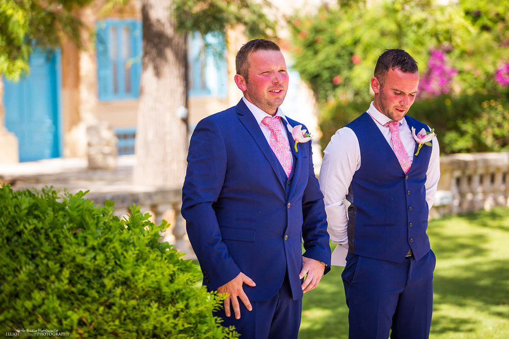 Groom stands with his bother the bestman and wait for his bride to arrive in the Baroque Gardens of the Villa Bologna, Malta.