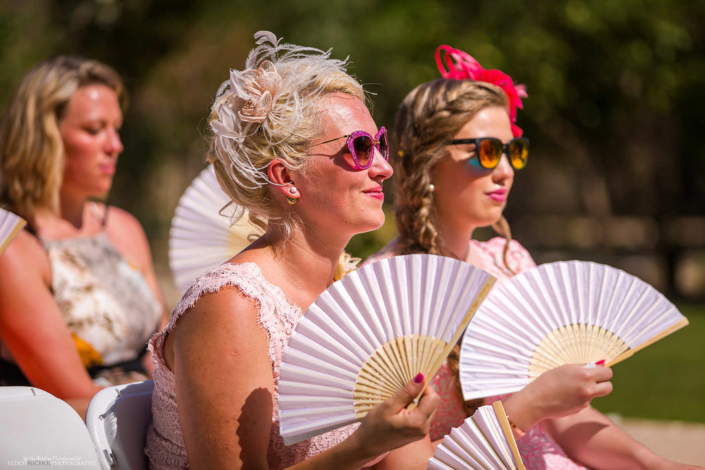 wedding guests using fans at a wedding ceremony at Villa Bologna, Malta