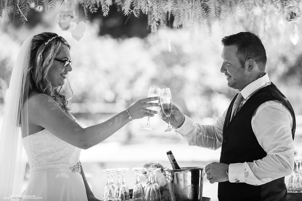 Husband and wife drink champagne after getting married at Villa Bologna