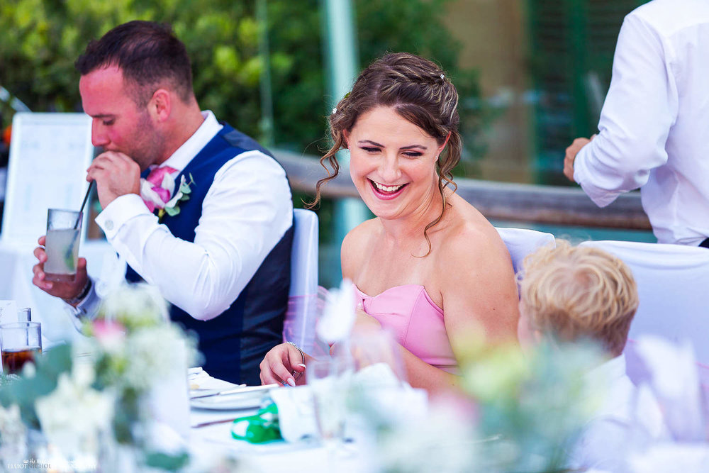 Bridesmaid laughing with guests at the wedding reception venue.
