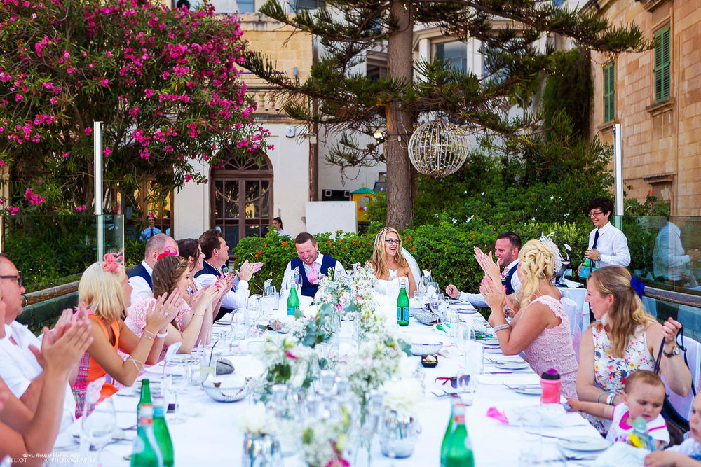 Bride and groom sit with their wedding guests at The Villa Brasserie in St Julians, Malta
