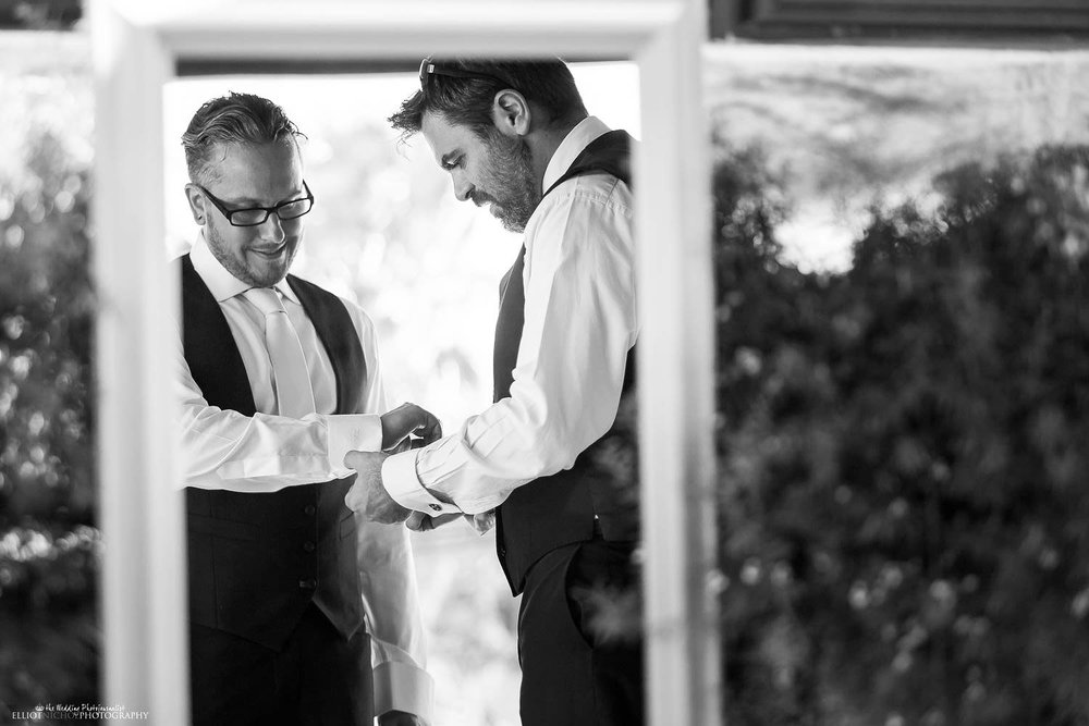 Bestman helping the groom put in his wedding cufflinks