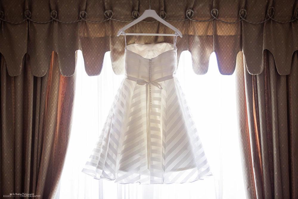 Brides short wedding dress hanging in the window of the bedroom in Malta