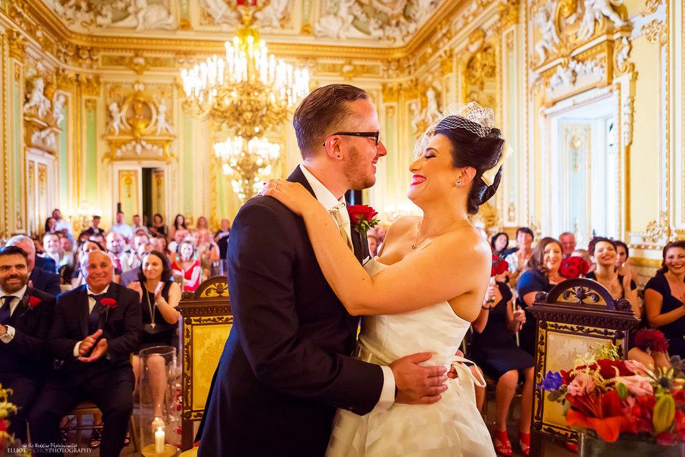Bride hugs her husband in the Ballroom of Palazzo Parisio