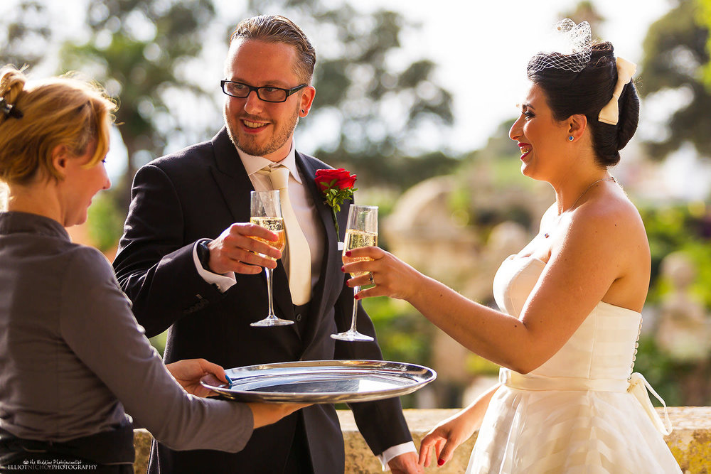 Bride and groom drink champagne to celebrate their wedding