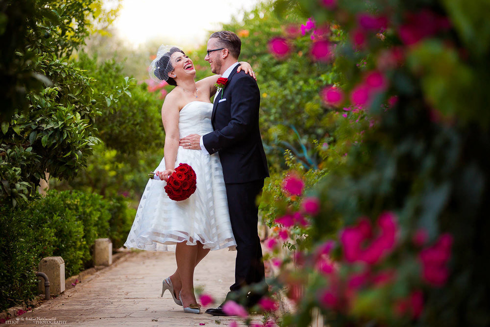 Bride and groom laughing in the Gardens of the Maltese wedding venue Palazzo Parisio.