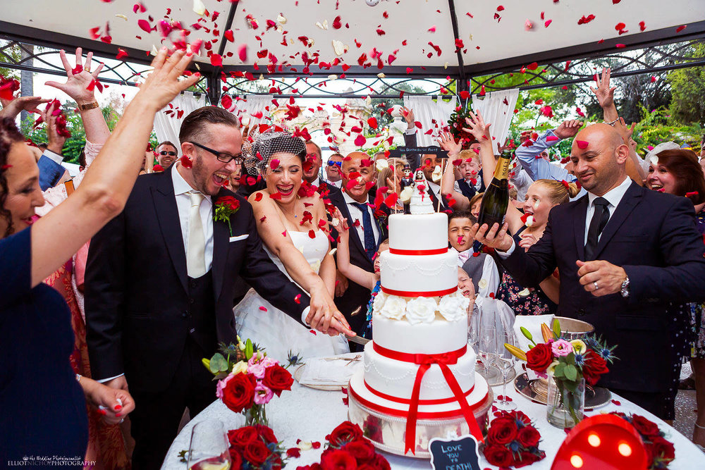Bride and groom cutting their wedding cake under a shower or red rose petals at the Palazzo Parisio in Malta.