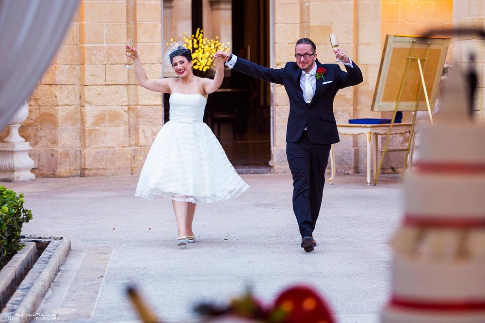 Bride and Groom make their entrance into their garden wedding reception at the Palazzo Parisio, Malta.