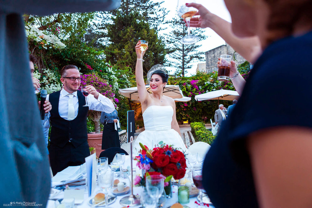 Bride and groom rise their glasses to toast the best man