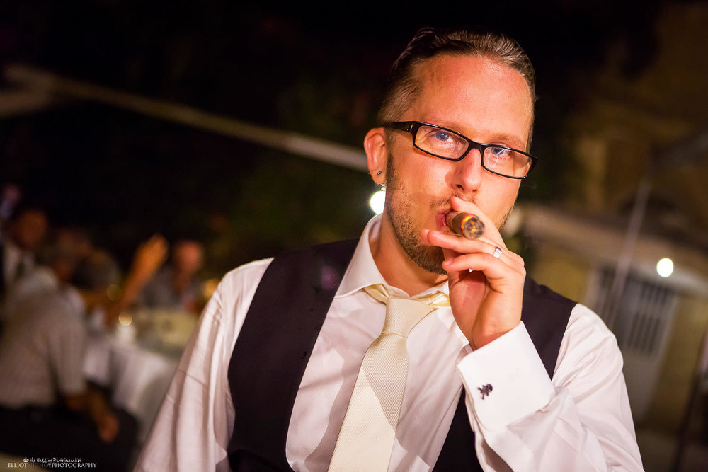 groom smoking a cigar at his wedding reception