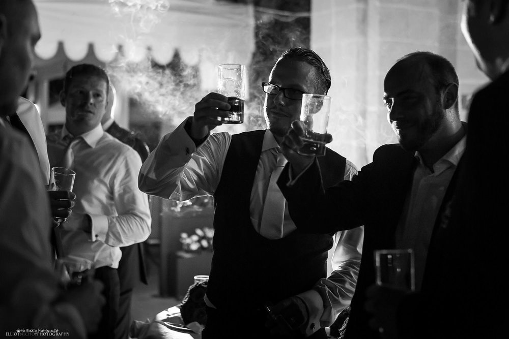 Groom and guests smoking cigars and drink brandy at the wedding reception