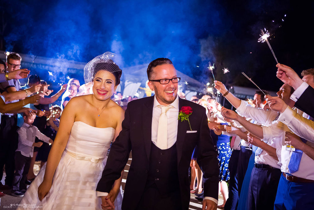 Bride and groom walk through an aisle of wedding guests holding sparklers at they depart the wedding venue Palazzo Parisio in Malta.
