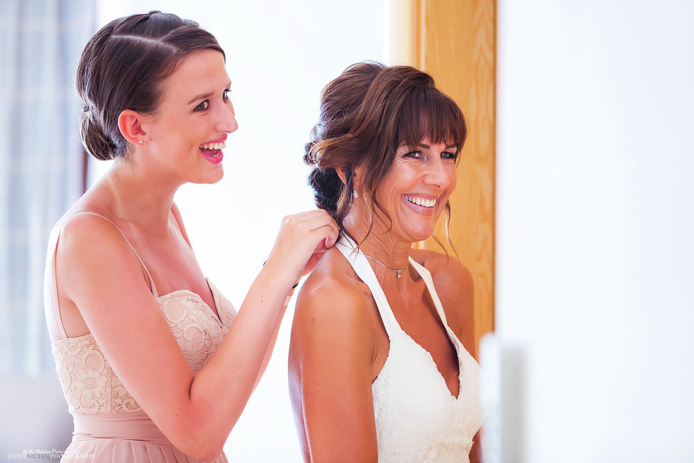 daughter helping put her mothers necklace on while getting ready on the wedding day.