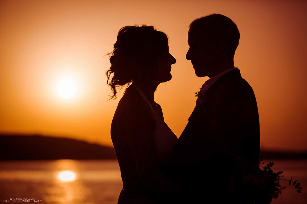Silhouette of bride and groom at sun sets in Malta.