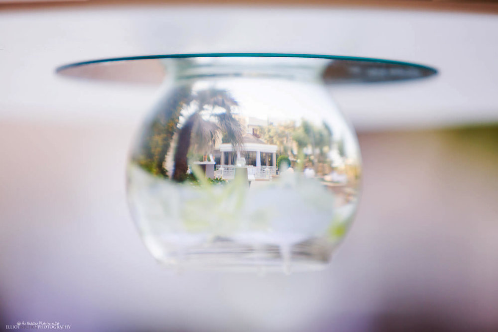 Reflection of the Villa Mdina wedding ceremony setup through a glass bowl filled with water.