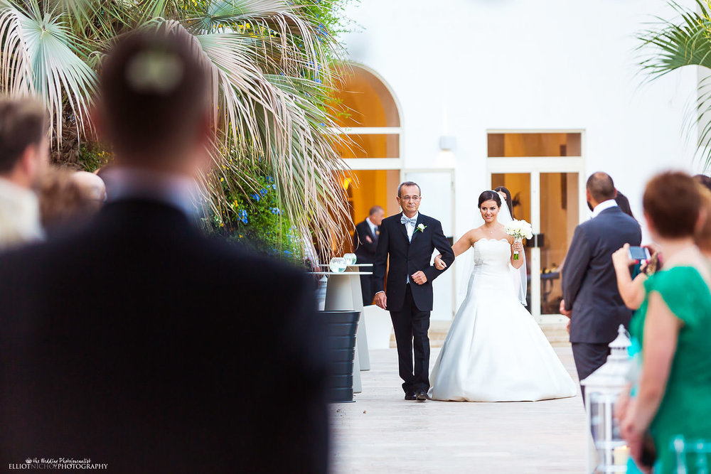 Bride arrives at the wedding ceremony with her father at Villa Mdina, Naxxar, Malta