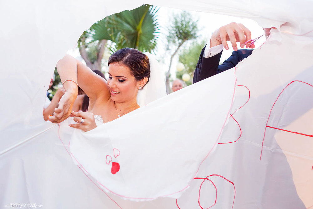 Bride and groom cut their through the wedding sheet