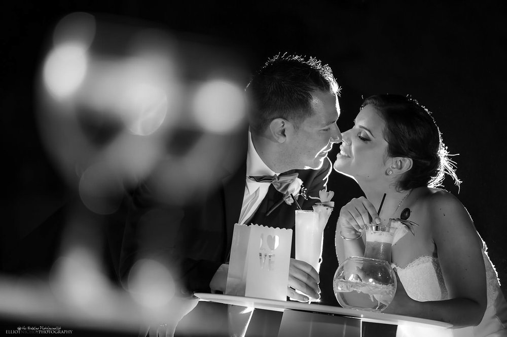 bride and groom kissing over wedding cocktails at their wedding reception at Villa Mdina, Naxxar, Malta
