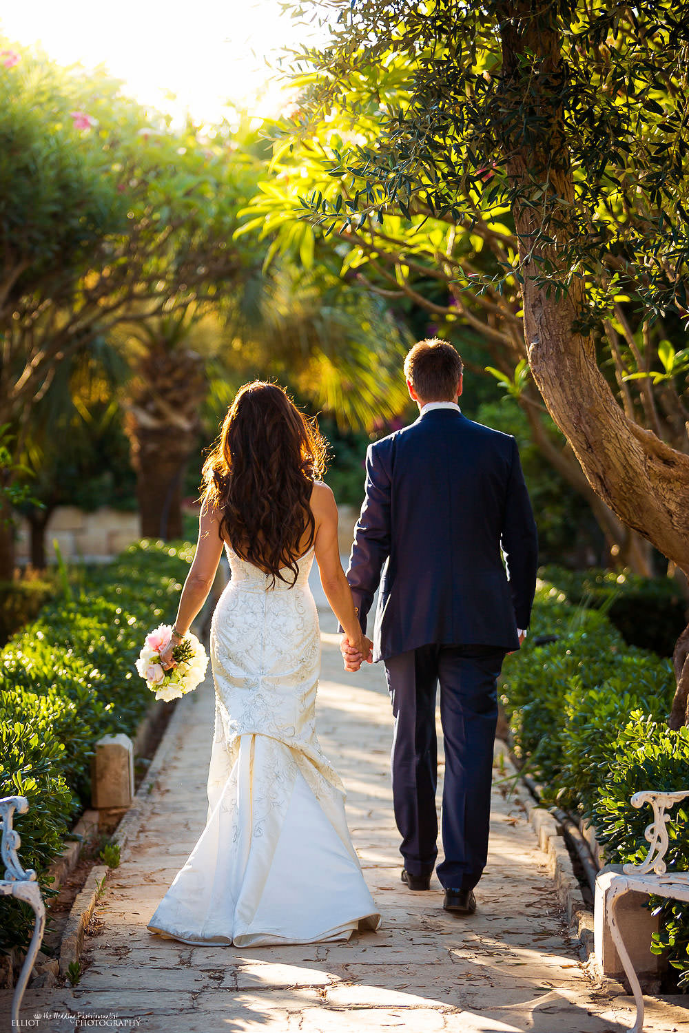 Bride and Groom walking through the gardens of the Palazzo Parisio in Malta. Photographer Elliot Nichol