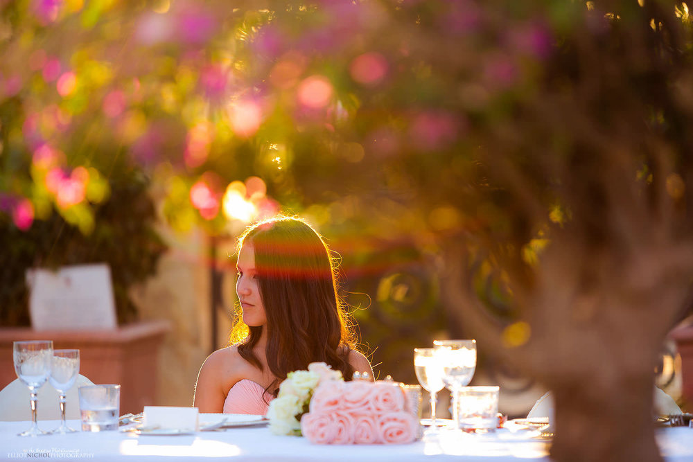 Wedding guest hit by golden sunlight during the garden wedding reception at the Palazzo Parisio in Malta. Photography by Elliot Nichol