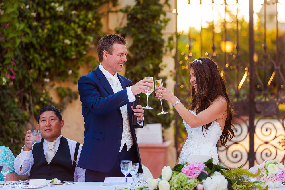 Bride and groom toast eachother during their wedding reception at the Palazzo Parisio in Malta