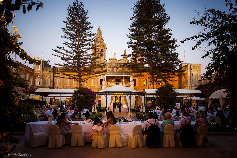 Garden wedding reception during dusk at the Palazzo Parisio in Malta. Wedding photography by Elliot Nichol.