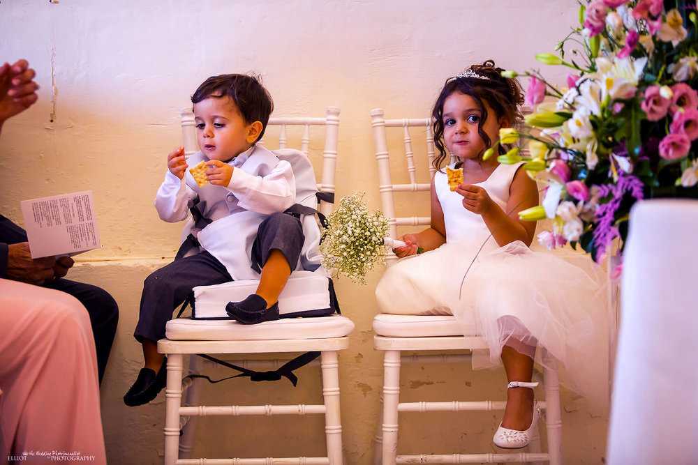 Bride and Groom's children enjoying some snacks during the wedding ceremony.
