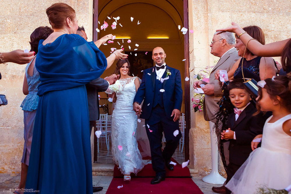 bride and groom leave the church under a shower of confetti