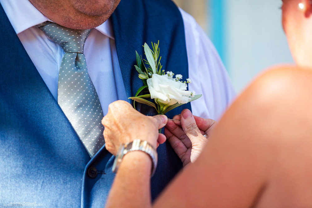 Groom having his flower button placed on his waistcoat.