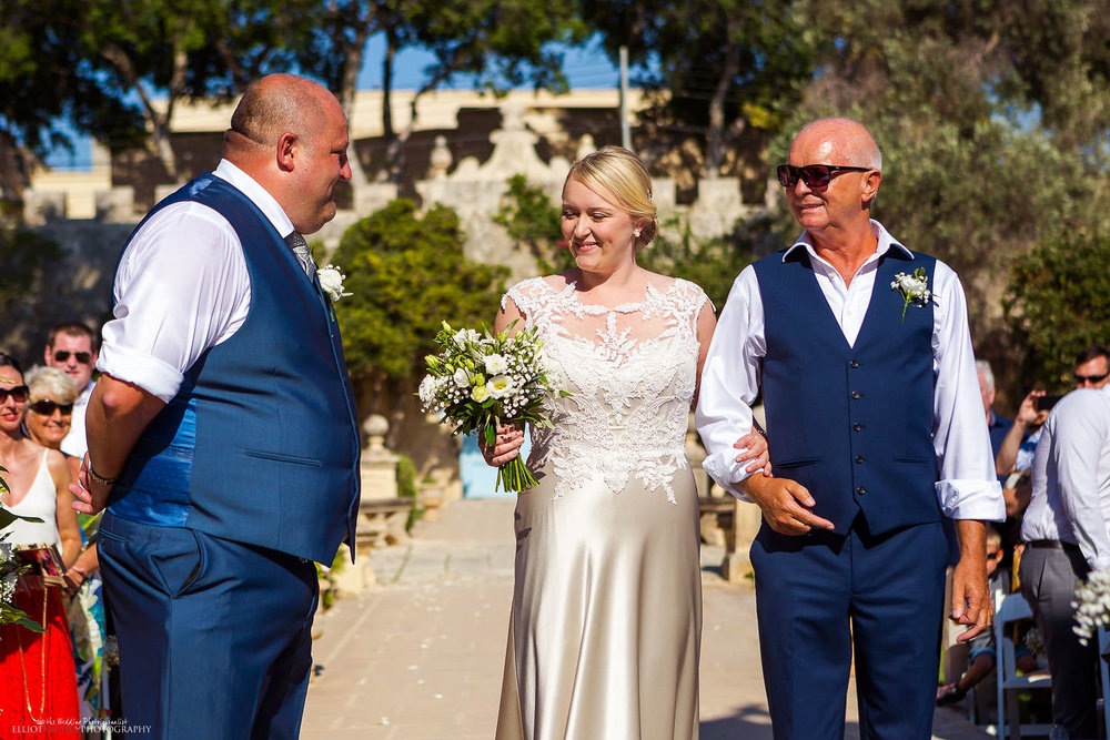 Bride arrives with her father to the wedding ceremony in the gardens of Villa Bologna, Malta.
