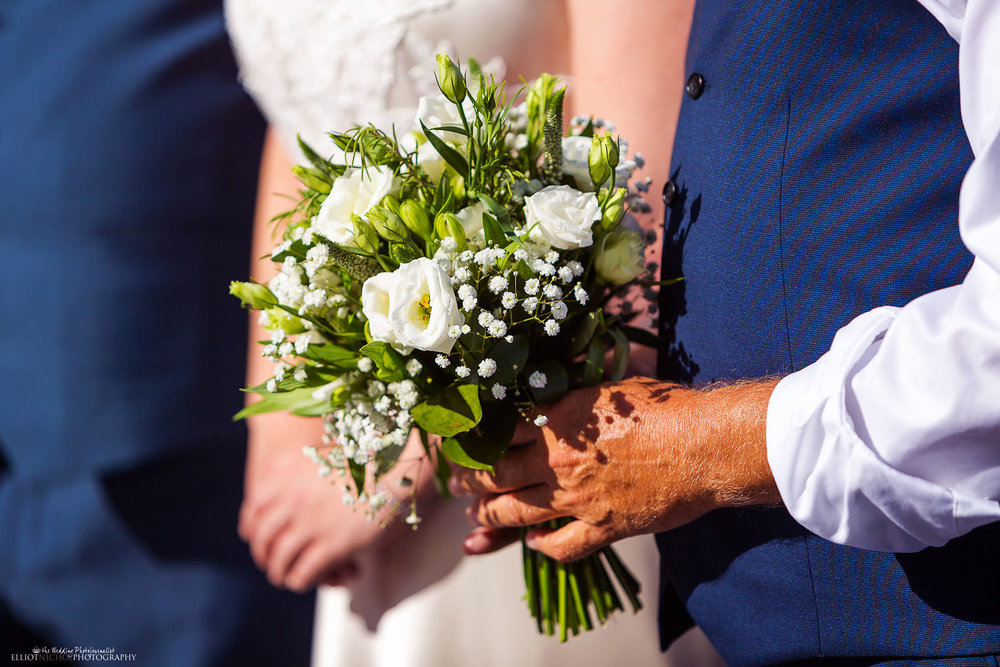 Father of the bride holds the bridal flower bouquet.
