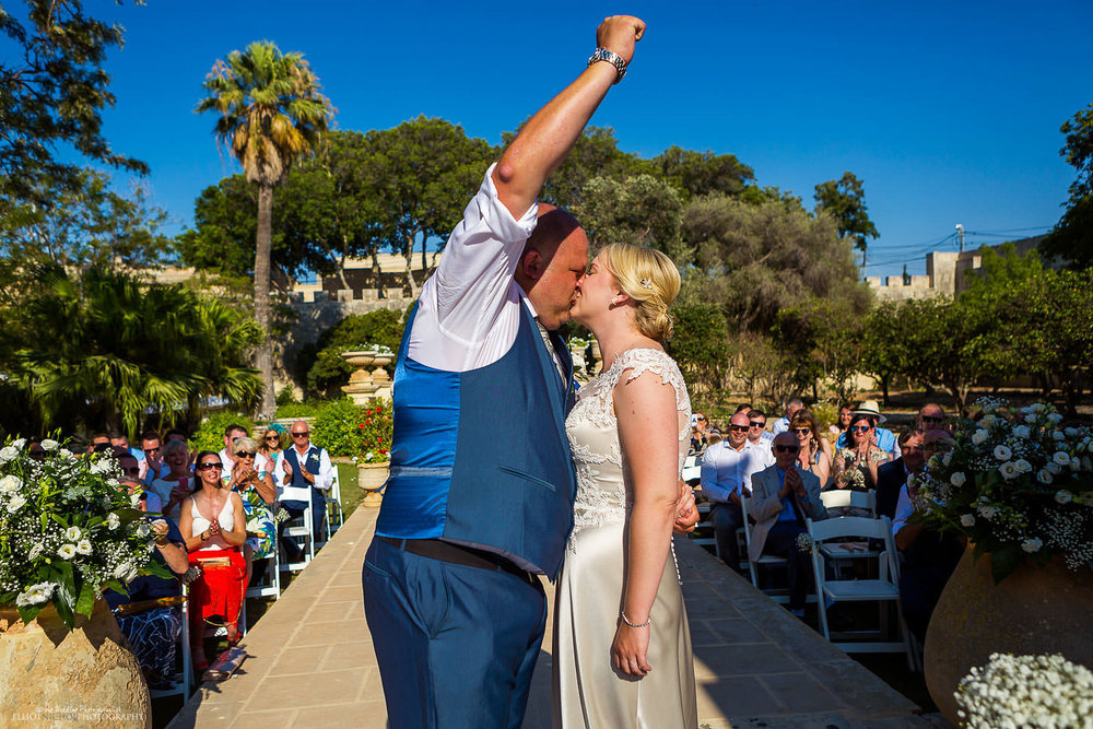Groom celebrates with a kiss at wedding ceremony at Villa Bologna, Malta.
