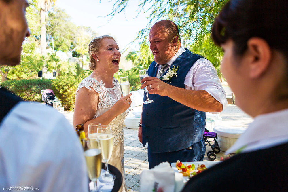Bride and groom drink champagne after getting married at Villa Bologna, Malta.