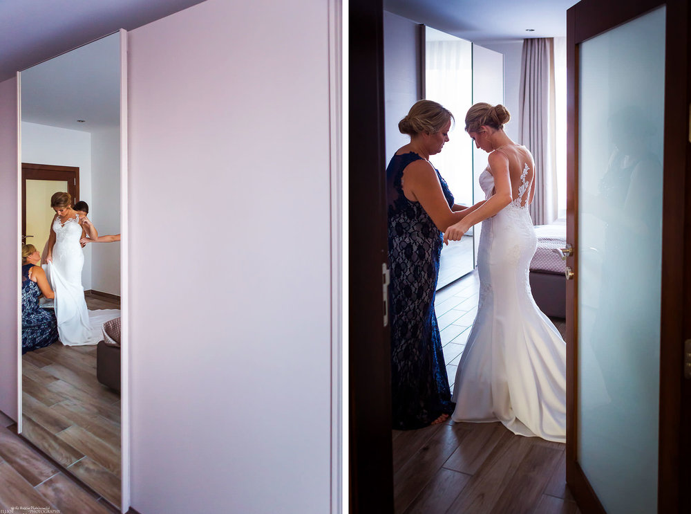 Mother of the bride helping her daughter into her wedding dress on her wedding day.