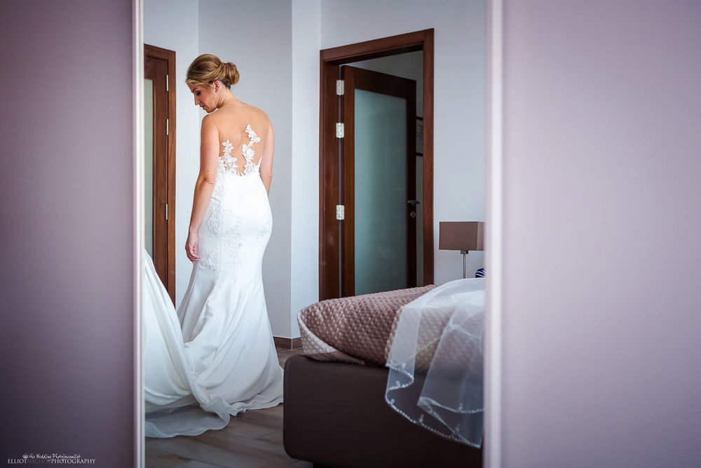 Bride reflected in mirror getting ready on her wedding day.