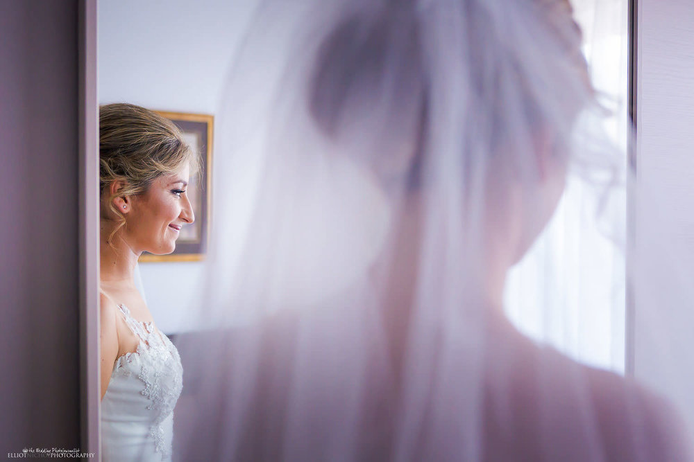 bride wearing her veil relfected in her bedroom mirror