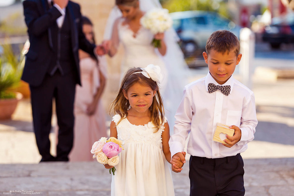 Flower girl and ring bearer walk towards the church