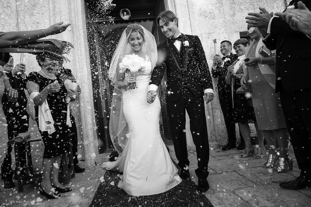 bride and groom leave the church under a shower of confetti in Malta.