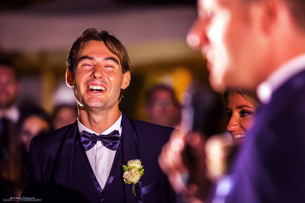 Groom laughs during his bestman's speech.