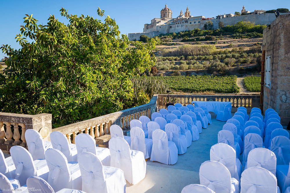 Wedding ceremony venue set up at the Olive Gardens with Mdina in the background.