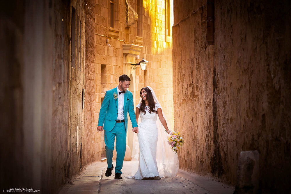 Bride and groom walk through the streets of Mdina, Malta. wedding photographer Elliot Nichol
